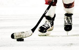 Hockey Skates and Stick on Ice